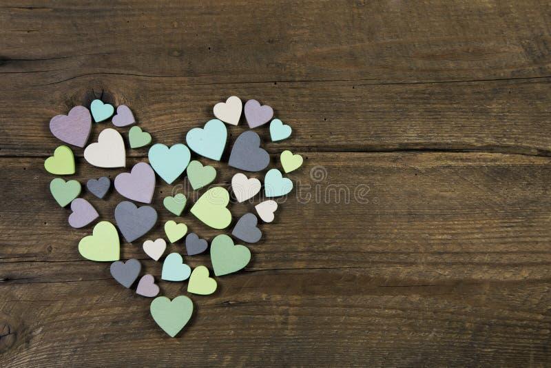 Sammlung vieler handgemachten Herzen in den natürlichen Farben auf altem Holz stockbild
