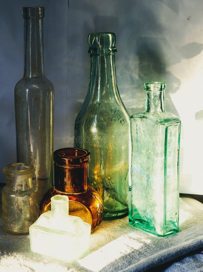 Sammlung Weinleseflaschen im Sonnenlicht mit Schatten Abschluss oben lizenzfreie stockbilder