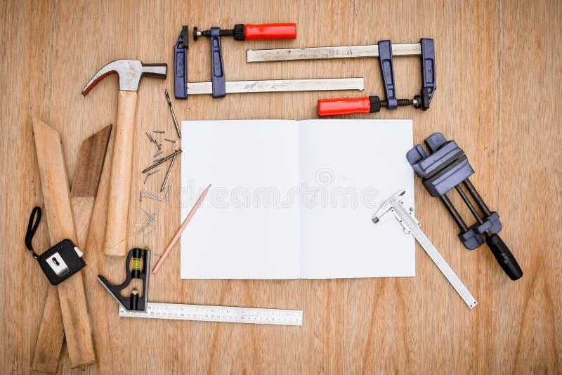 Sammlung worktools, Satz Arbeitsgeräte (Stahlschlüssel, Hammer, Nägel, Bolzen, Schlüssel, usw. ) mit Notizbuch auf dem hölzernen  lizenzfreies stockbild