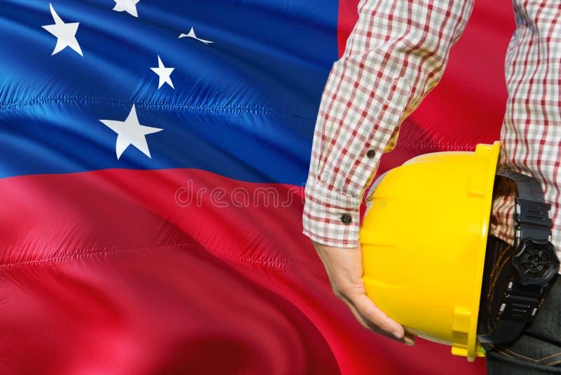 Samoański inżynier trzyma żółtego zbawczego hełm z machać Samoa chorągwianego tło Budowy i budynku poj?cie obrazy stock