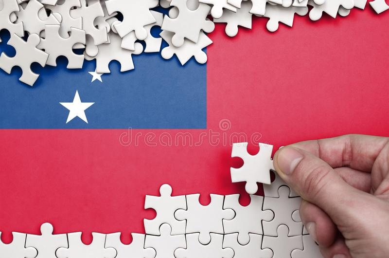 Samoa flag is depicted on a table on which the human hand folds a puzzle of white color royalty free stock image