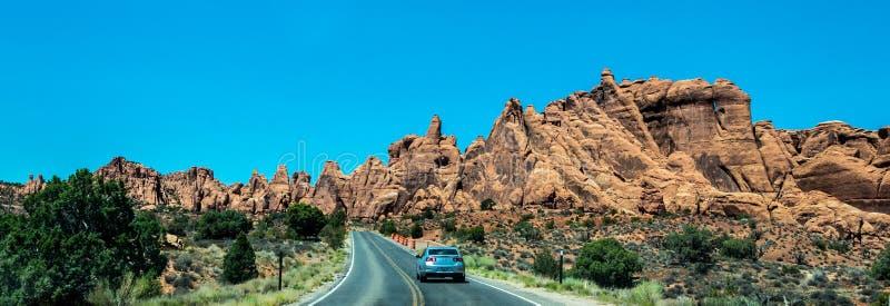 Samochód na autostradzie w łukach parki narodowi, Utah, usa Lato wycieczka naturalni przyciągania Ameryka zdjęcia stock