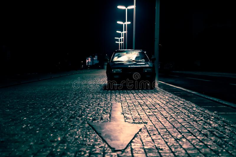 Samochód na brukującej ulicie z strzałą wskazuje w ciemnej strasznej ulicie, Zadar, Chorwacja obrazy royalty free