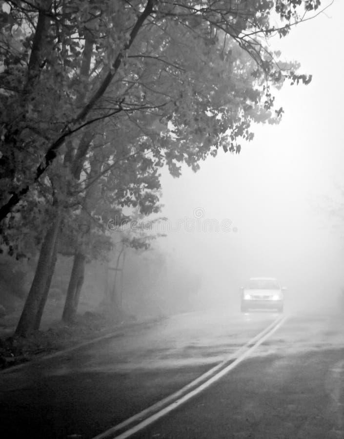 Samochód na drodze w mgle Jesień krajobraz zdjęcia stock