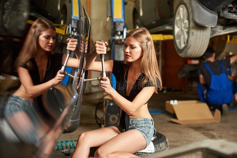 Samochód naprawa wykonująca dziewczyną z spanner w ona ręki obraz royalty free