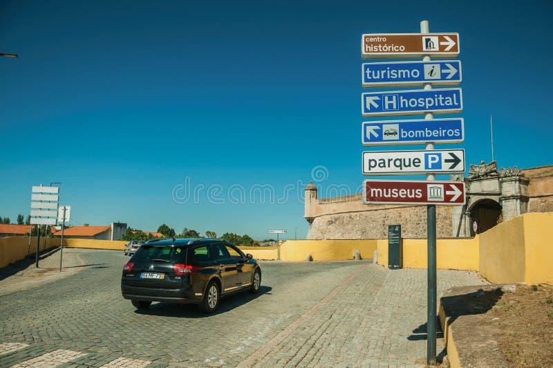 Samochód w ulicie z kierunkowskaz wskazującymi służbami publicznymi i miast przyciąganiami przy Elvas zdjęcia royalty free
