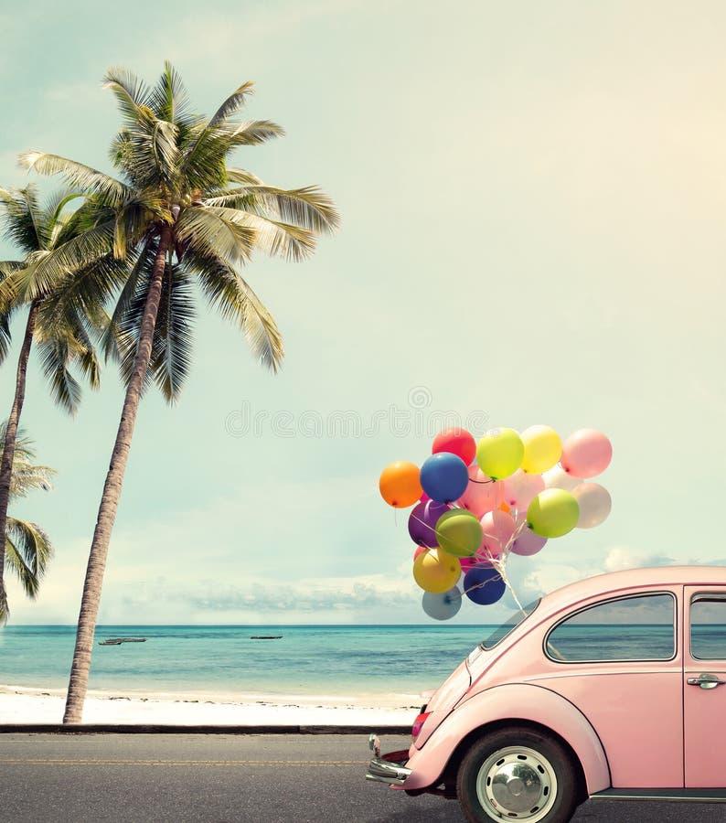 Samochód z kolorowym balonem na plażowym niebieskim niebie fotografia royalty free
