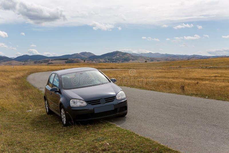 Samochód z podróżników stojakami na poboczu w koloru żółtego polu w zabljak w Montenegro fotografia stock