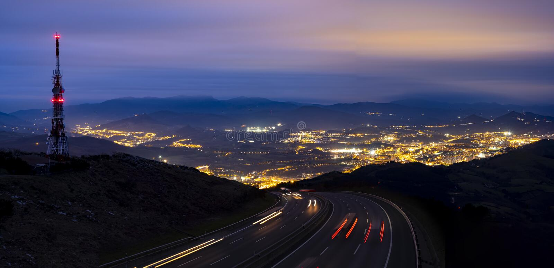 Samochód zaświeca miasto przy nocą i teletechniczny wierza obraz royalty free