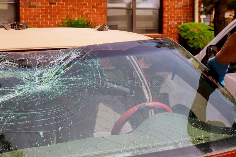 Samochodów specjalni pracownicy usuwają łamanego windscreen lub przednią szybę samochód w auto stacja obsługi fotografia royalty free