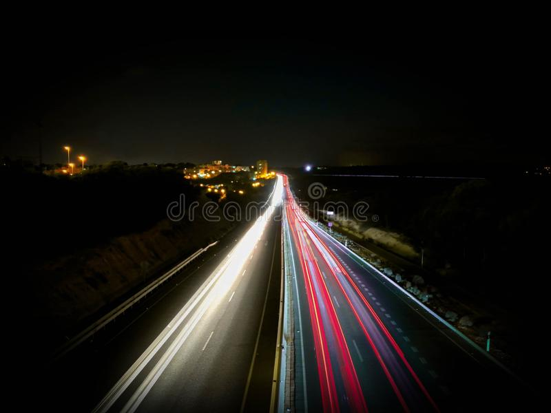 Samochod?w ?wiat?a na przekazie i autostradzie g?ruj? przy noc?, d?uga ujawnienie fotografia ruch drogowy fotografia royalty free