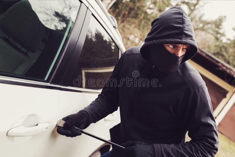Samochodowa kradzież - złodziej próbuje łamać w pojazd zdjęcia stock