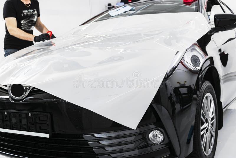 Samochodowa opakunkowa specjalisty kładzenia winylu folia lub film na samochodzie Ochronny film na samochodzie Stosować ochronneg obraz royalty free