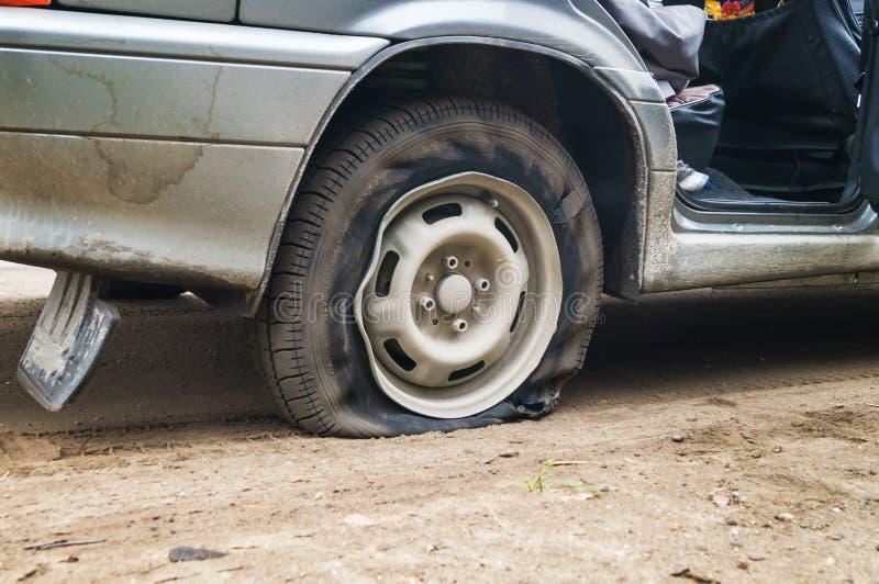 Samochodowa płaska opona na złej drodze obraz royalty free