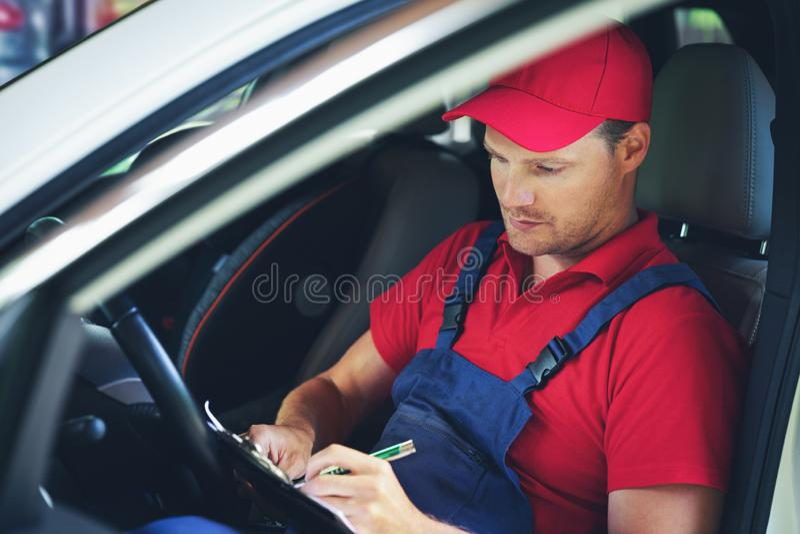Samochodowego mechanika obsiadanie wśrodku samochodu i pisać wizytacyjnych dokumentach na schowku fotografia royalty free