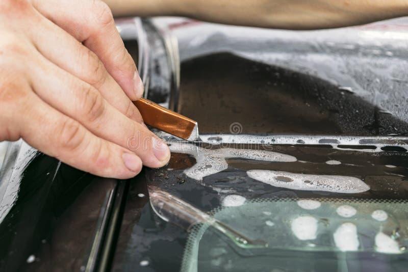 Samochodowego opakunkowego specjalisty winylu tnąca folia lub film na samochodzie Ochronny film na samochodzie Stosować ochronneg zdjęcia royalty free