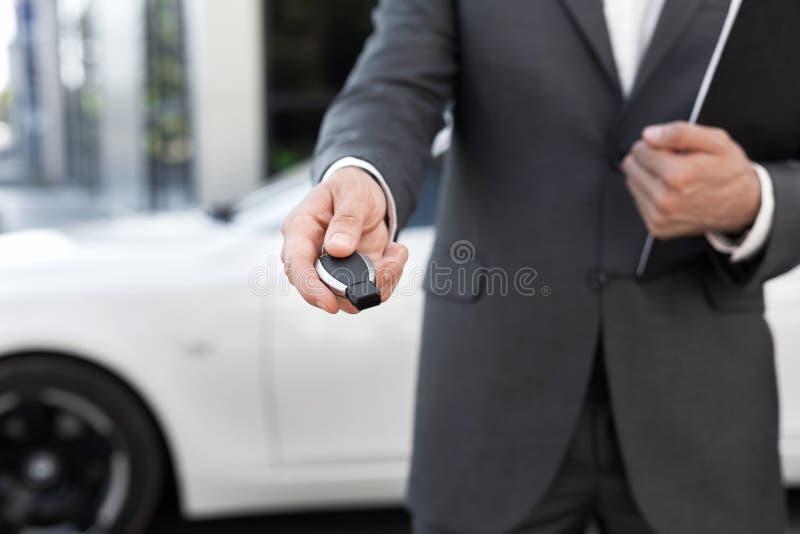 Samochodowego sprzedawcy mienia klucz i przedstawiać nowego samochód obrazy stock