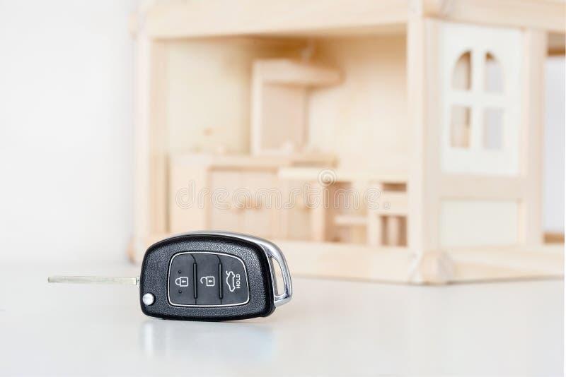 Samochodowi klucze z drewnianym domem modelują na tle Wybór byuing podstawowa potrzeba Decyzja priorytetu lub prasmoły koniecznoś fotografia stock
