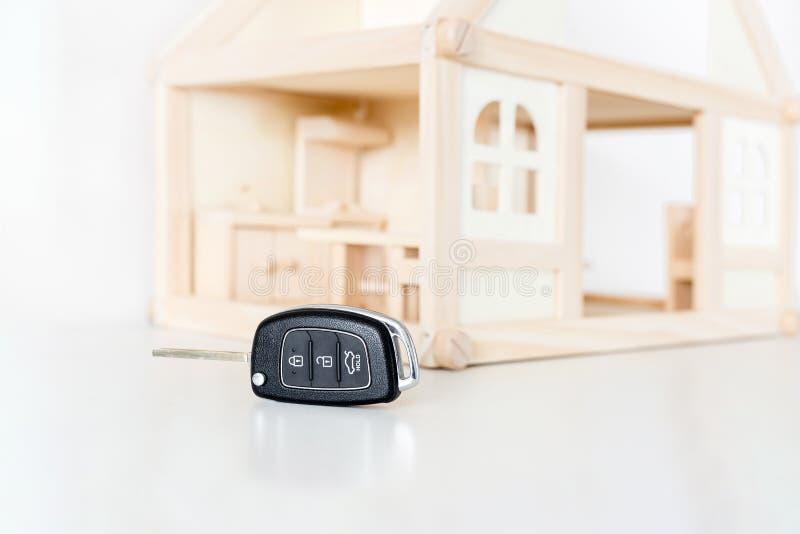 Samochodowi klucze z drewnianym domem modelują na tle Wybór byuing podstawowa potrzeba Decyzja priorytetu lub prasmoły koniecznoś zdjęcia royalty free