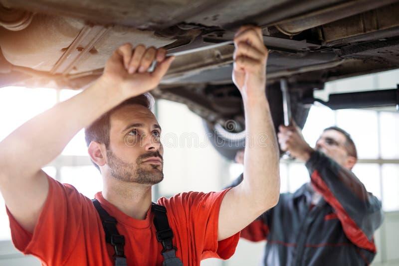 Samochodowi mechanicy pracuje przy automobilowym usługowym centrum zdjęcie royalty free