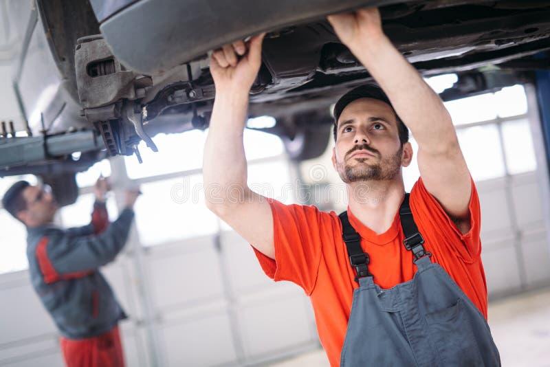 Samochodowi mechanicy pracuje przy automobilowym usługowym centrum zdjęcia stock