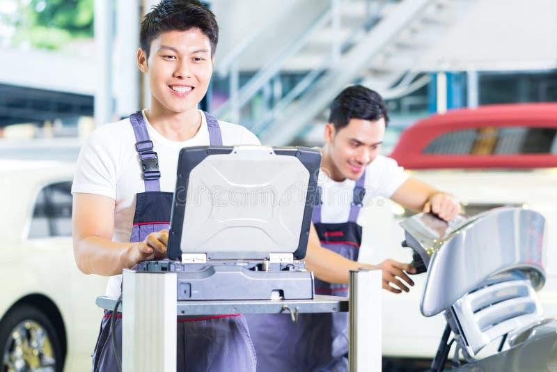 Samochodowi mechanicy z diagnozy narzędziem w Azjatyckim auto warsztacie zdjęcia royalty free