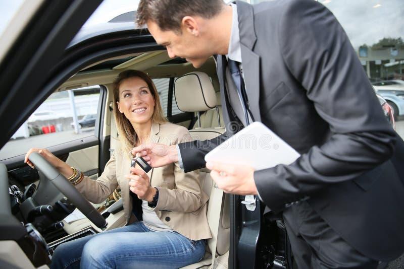 Samochodowy delaer wręcza klucz szczęśliwy właściciel obraz stock