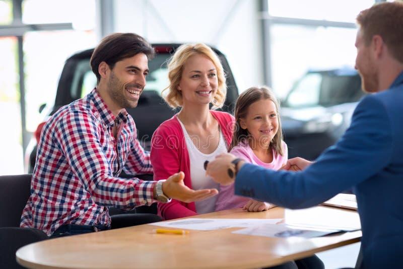 Samochodowy handlowiec sprzedaje nowego samochód młoda rodzina z dzieckiem fotografia royalty free