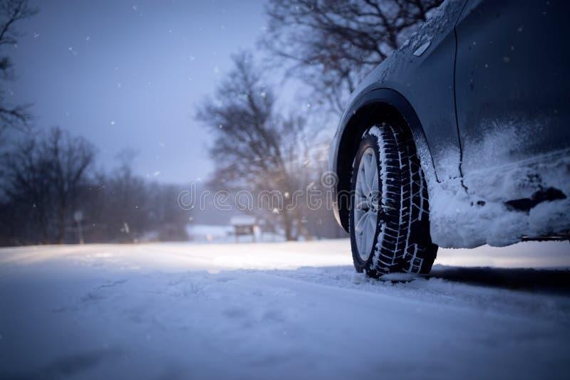 Samochodowy i spada śnieg w zimie na lasowej drodze fotografia stock