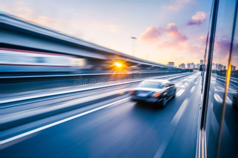 Samochodowy jeżdżenie na autostradzie przy zmierzchem, ruch plama fotografia stock