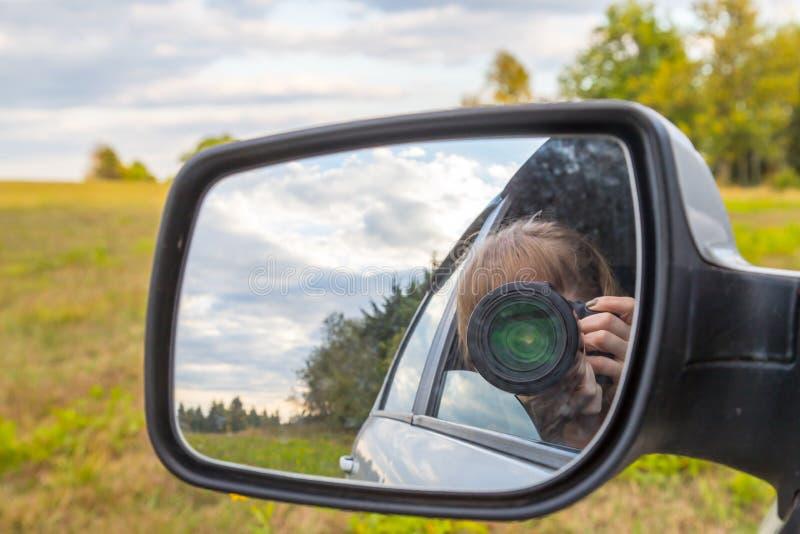 Samochodowy lustro odbicie żeński fotograf w nim i krajobraz z, polem i drzewem obraz stock