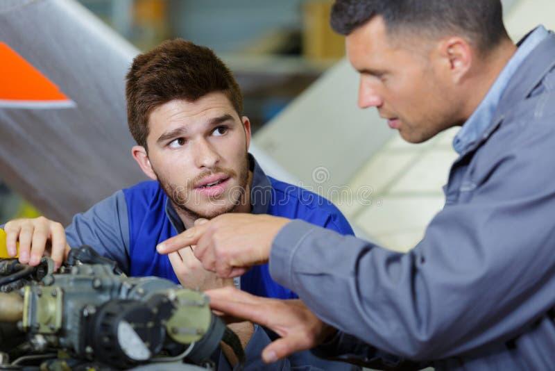 Samochodowy mechanik bada samochodowego silnika w remontowym garażu zdjęcia royalty free