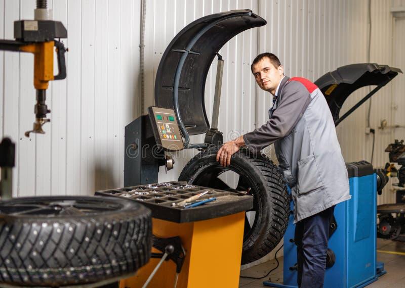 Samochodowy mechanik balansuje samochodowego koło na balancer w auto remontowej usługa obrazy stock