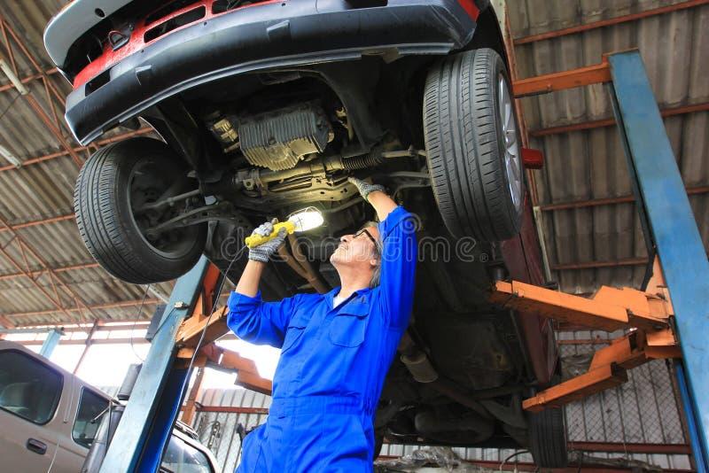 Samochodowy mechanik egzamininuje samoch?d u?ywa? latark? w auto remontowej us?udze obraz royalty free