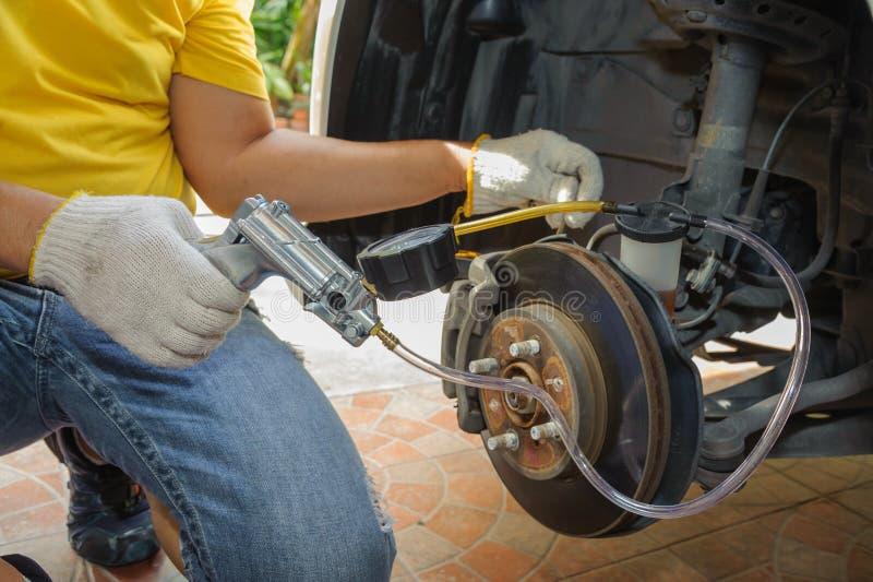 Samochodowy mechanik krwawi powietrze z hamulcowego systemu obraz stock