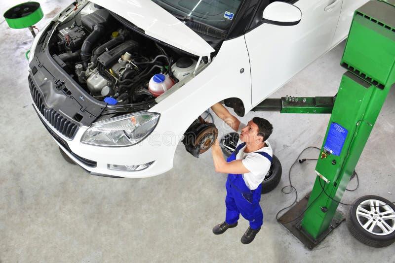 Samochodowy mechanik naprawia hamulce pojazd na podnośnej platformie fotografia royalty free