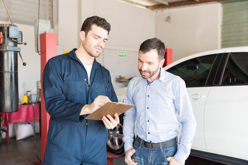 Samochodowy mechanik Pokazuje utrzymanie listę kontrolną klient W garażu zdjęcia stock