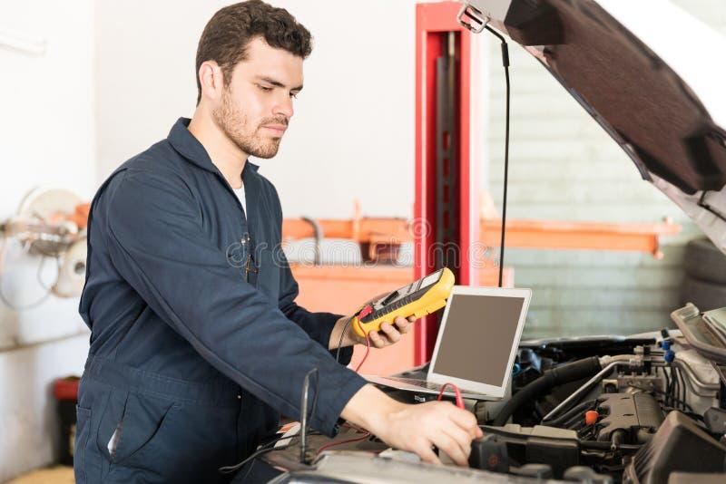 Samochodowy mechanik Sprawdza woltaż Bateryjny Używa Voltmeter zdjęcia stock