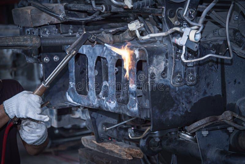 Samochodowy mechanik z wyrwaniem w garażu Pracownicy spawają auto części obrazy royalty free