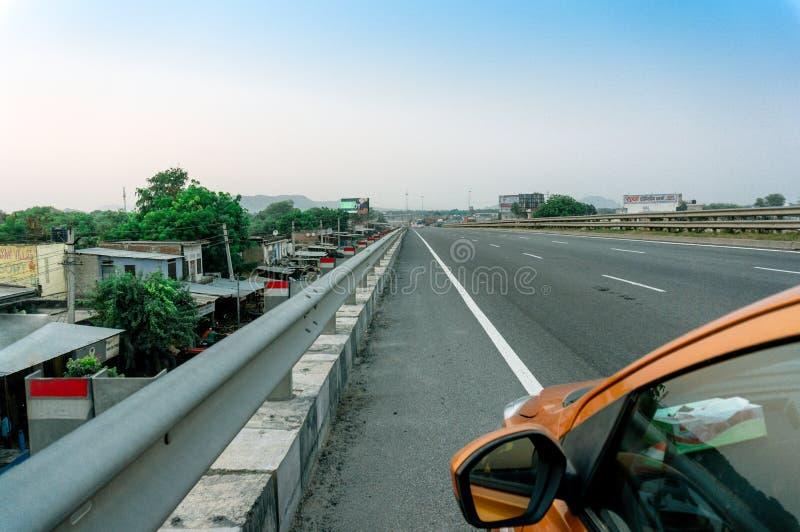 Samochodowy obszycie długa droga z chmurnymi niebami, domy i góra zdjęcia stock