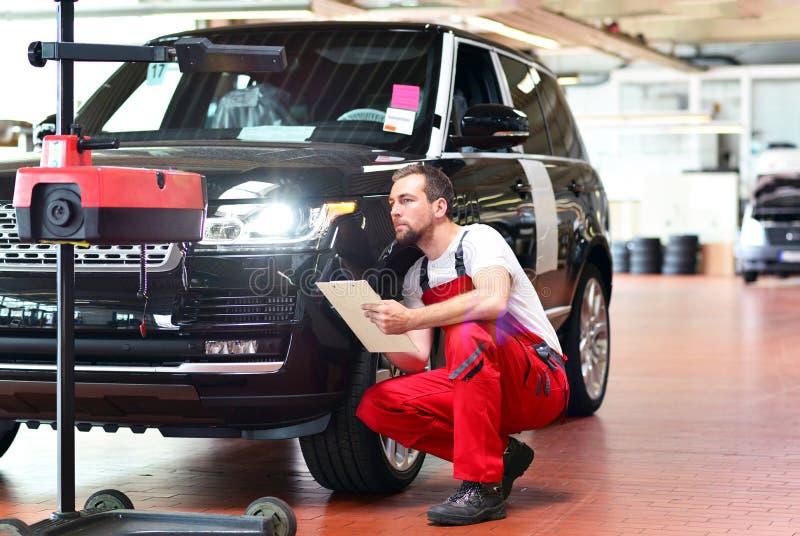 Samochodowy remontowy sklep - pracownik sprawdza reflektory a i przystosowywa zdjęcie royalty free