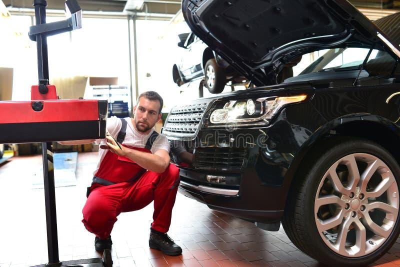 Samochodowy remontowy sklep - pracownik sprawdza reflektory a i przystosowywa obraz stock