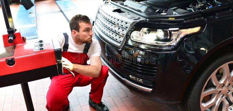 Samochodowy remontowy sklep - pracownik sprawdza reflektory a i przystosowywa obrazy stock