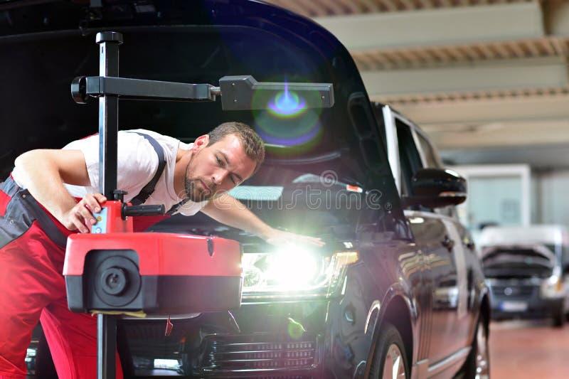 Samochodowy remontowy sklep - pracownik sprawdza reflektory a i przystosowywa obraz royalty free