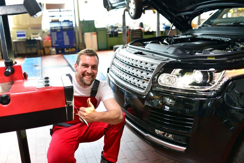 Samochodowy remontowy sklep - pracownik sprawdza reflektory a i przystosowywa obrazy royalty free