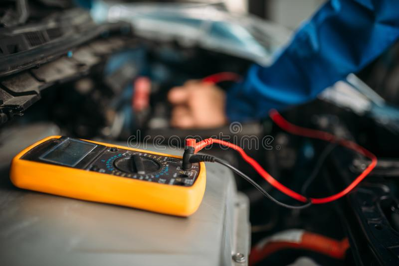 Samochodowy repairman z multimeter, bateryjna inspekcja fotografia royalty free