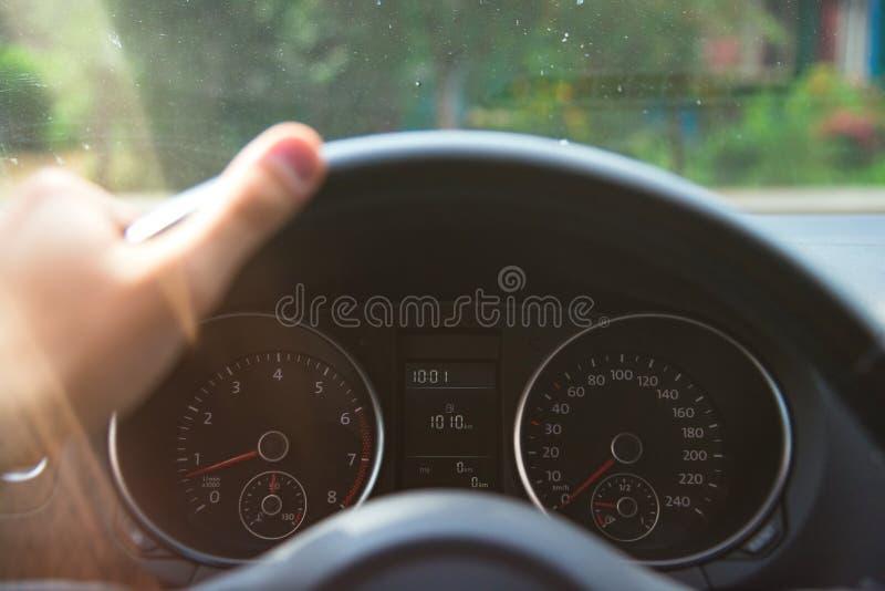 Samochodowy speedometr z (0) km na nim i ręką na stearwheel pod ranku zmierzchem zaświeca zdjęcia stock