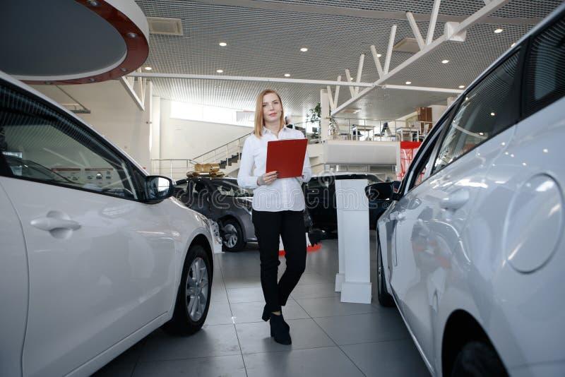 Samochodowy sprzedawca w kostiumu przy samochodową sala wystawową pokazuje pięknej eleganckiej dziewczyny na pastylki informaci P obraz royalty free