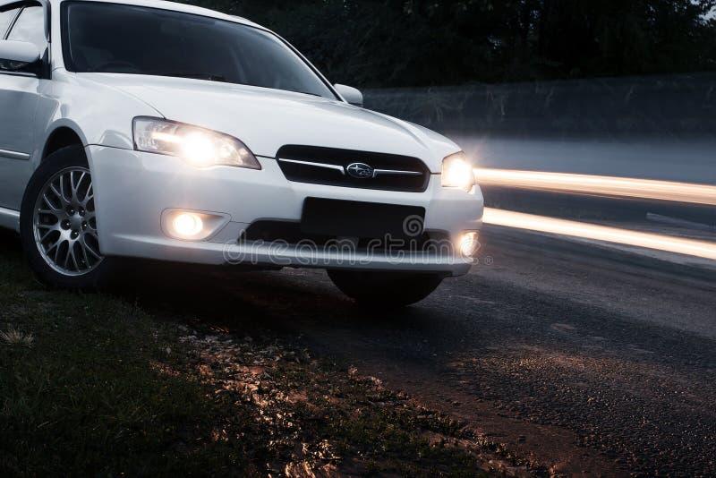 Samochodowy Subaru spadku pobyt na asfaltowej drodze blisko przelotnych samochodów przy półmrokiem obrazy royalty free