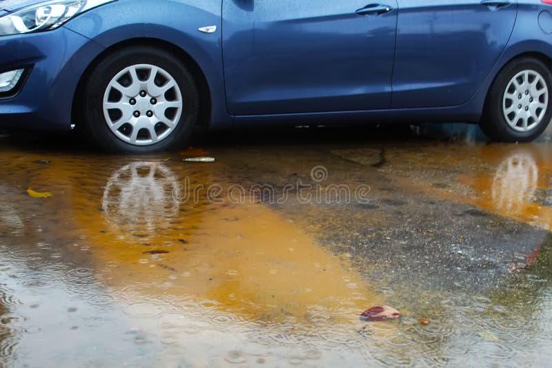 Samochodowy toczy wewnątrz kałużę deszczówka, raindrops i woda okręgi, Zimy pogoda w Izrael zdjęcia stock
